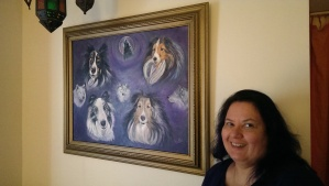 Caryn next to a portrait of her Shetland Sheepdogs